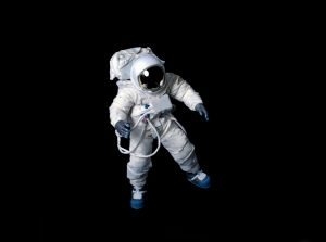 Astronaut wearing a plain pressure suit without symbols or insignia against a black background.